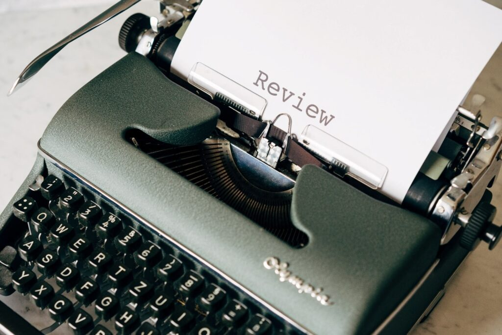 black typewriter with review written on a paper